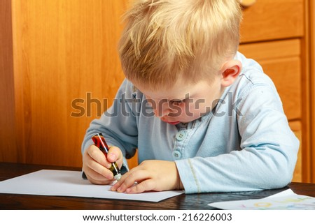 Happy childhood. Blonde boy child kid with pen writing drawing on paper doing homework. At home. - stock photo