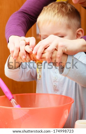 Happy childhood. Boy kid baking cake. Mother young woman teaching showing her son child how breaking egg into a bowl. Kitchen. Real. - stock photo