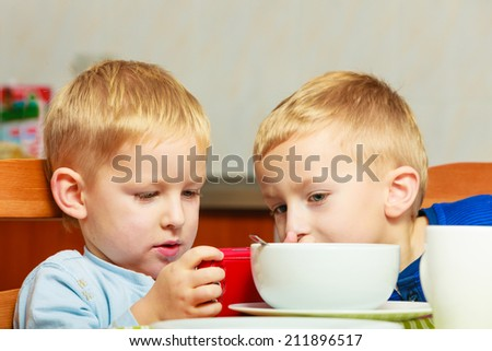 Happy childhood. Boys kids children eating corn flakes cereal with milk breakfast morning meal. Brothers playing with mobile phone at the table. Home. - stock photo