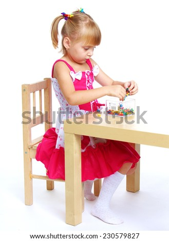 happy childhood, Montessori teaching concept.little girl in a Montessori school.Isolated on white background. - stock photo