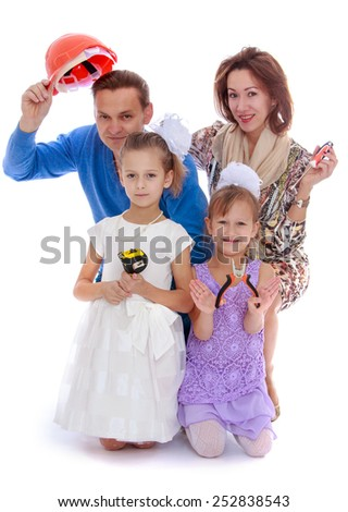 Happy childhood, the family concept.Cheerful family with two daughters holding various construction tools. Isolated on white. - stock photo