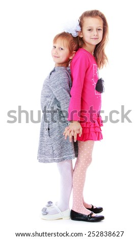 Happy childhood, the family concept.Cute girls are standing back to back. Isolated on white. - stock photo