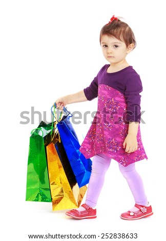 Happy childhood, the family concept.Cute serious girl is in front of a colorful packages.Isolated on white. - stock photo