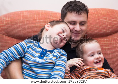 Happy children boys and daddy having fun on sofa at home - stock photo
