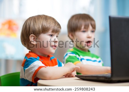happy children boys working at laptop indoors - stock photo