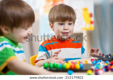 happy children brothers play together at table - stock photo