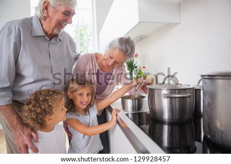Happy children cooking with grandparents in the kitchen - stock photo