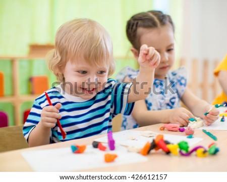 Happy children doing arts and crafts. Kids in kindergarten. - stock photo