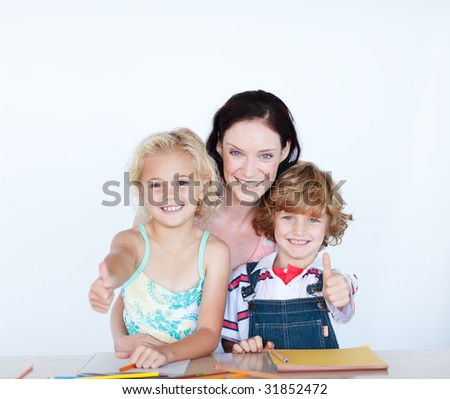 Happy children doing homework with their mother with thumbs up - stock photo