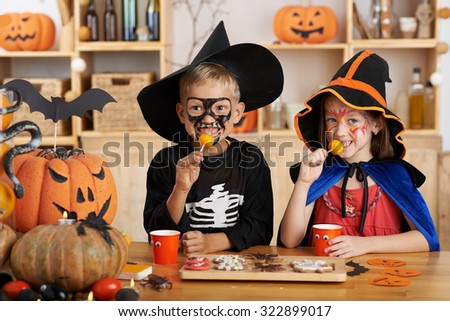 Happy children eating Halloween treats at the party - stock photo