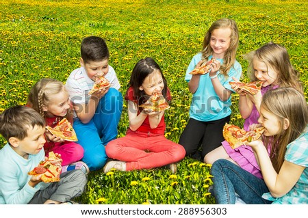 Happy children eating pizza outdoors - stock photo