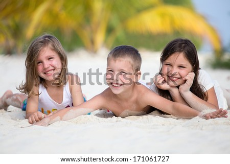 Happy children enjoy summer day at the beach - stock photo