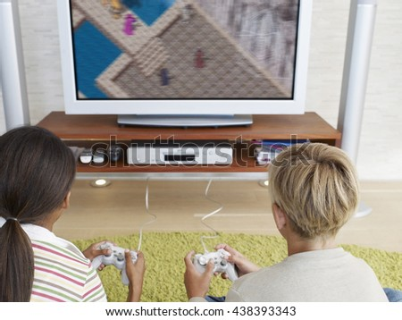 Happy children - girl and boy playing a video game at home - stock photo