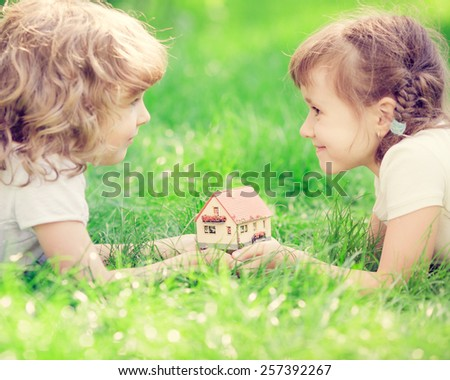 Happy children holding model house in hands. Kids lying on green grass in spring park. New home concept - stock photo