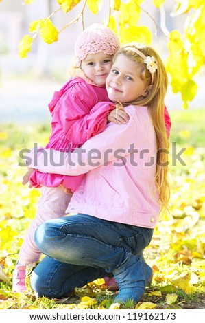 Happy children hugging in the autumn park - stock photo