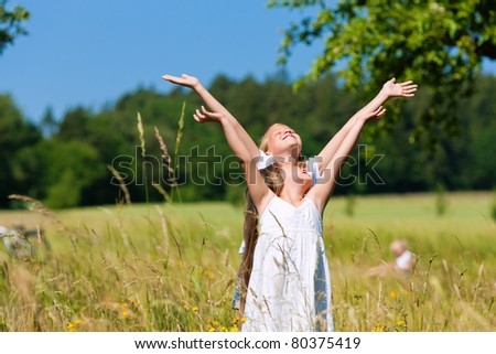 Happy children in a meadow in summer - stock photo