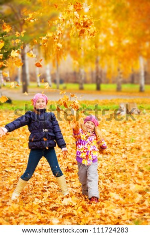 Happy children in autumn park. Kids juggle leaves - stock photo