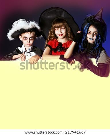 Happy children in halloween costumes posing over dark background. Copy space. - stock photo