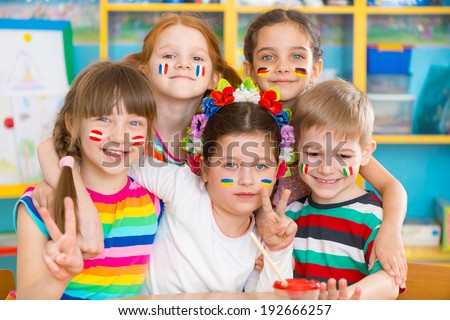Happy children in language camp with flags on cheeks - stock photo