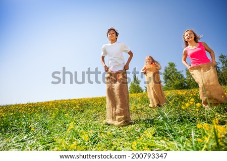 Happy children jumping in sacks during play - stock photo