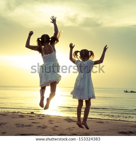 Happy children jumping on the beach on the dawn time - stock photo