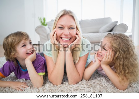 Happy children looking at mother lying on rug at home - stock photo