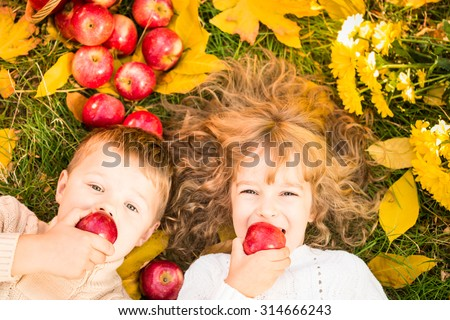 Happy children lying on fall leaves. Funny kids outdoors in autumn park - stock photo