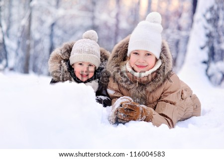 happy children lying on the snow in winter - stock photo