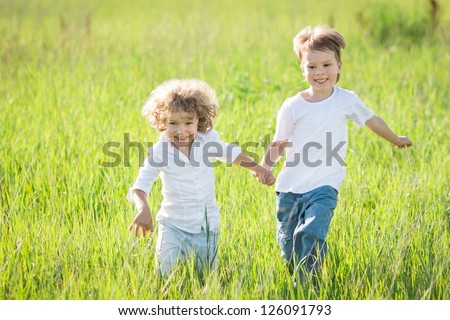 Happy children playing in spring field - stock photo
