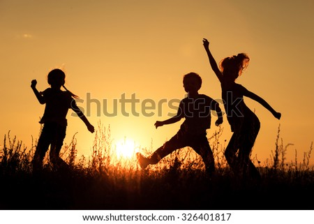 Happy children playing in the park at the sunset time. - stock photo