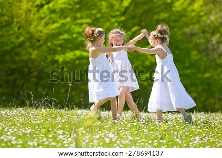 Happy children playing  on green grass in spring park - stock photo