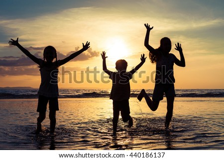 Happy children playing on the beach at the sunset time. Concept of friendly family. - stock photo