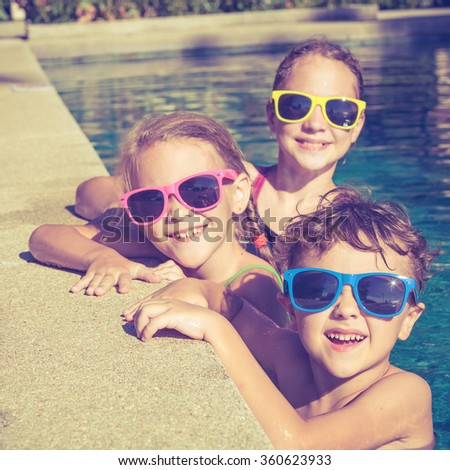 happy children  playing on the swimming pool at the day time. Concept of friendly family. - stock photo