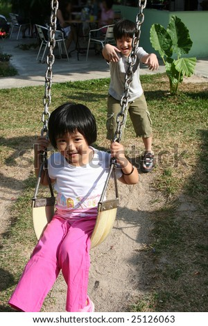 Happy children playing swing at the playground in the park on sunny day - stock photo