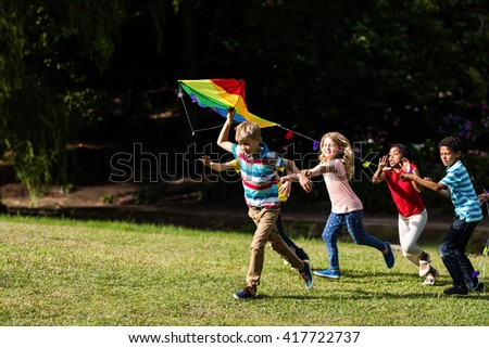 Happy children playing with a kite in the park - stock photo