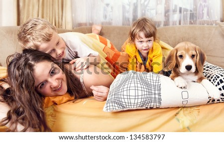 Happy children playing with beagle puppy in bed - stock photo