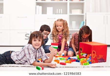 Happy children playing with blocks - focus on the boy - stock photo