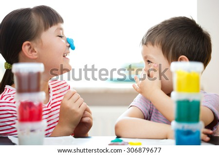 Happy children playing with color play dough - stock photo
