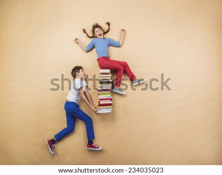 Happy children playing with group of books in studio - stock photo