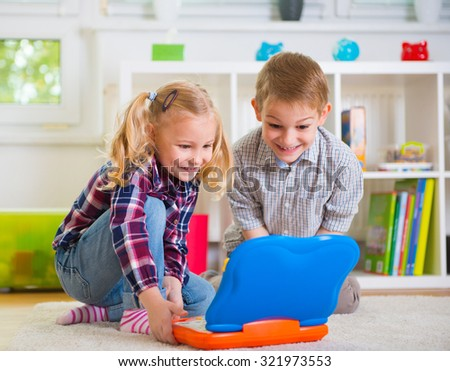 Happy children playing with toy laptop at home - stock photo