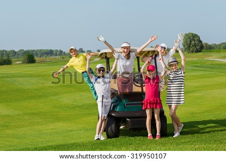 Happy children posing near golf car at golf course at summer day - stock photo