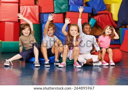 Happy children raising their hands in gym of an elementary school - stock photo