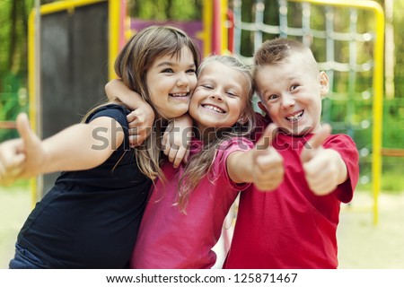 Happy children showing ok sign on playground - stock photo
