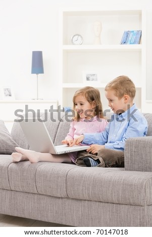 Happy children sitting on couch at home, browsing internet on laptop computer, looking at screen smiling.? - stock photo