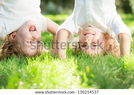 Happy children standing upside down on green grass in spring park. Healthy lifestyles concept. - stock photo