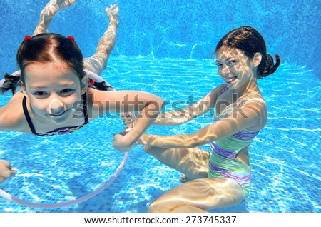 Happy children swim in pool underwater, girls swimming, playing and having fun, kids water sport  - stock photo