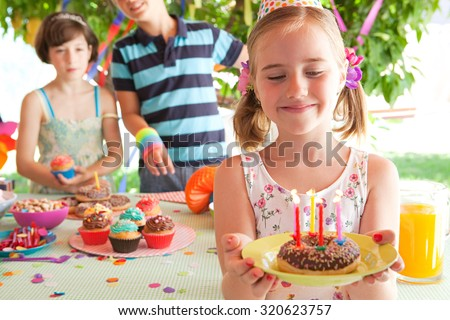 Happy children together, celebrating a colorful birthday party in a home garden with decorations, home outdoors. Proud girl holding birthday cake with candles. Kids fun active lifestyle, exterior. - stock photo