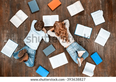 Happy children. Top view creative photo of little boy and girl on vintage brown wooden floor. Children lying near books and reading it - stock photo