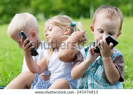 Happy children using smartphones sitting on the grass. Brothers and sister. - stock photo