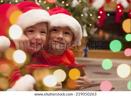 Happy children with Christmas gift - stock photo